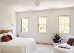 Room with bed, round pillows, lounge chair and three evenly spaced windows on wall