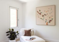 Lounge chair with pillows, open book on top, next to window and framed art on the wall and potted plant on floor